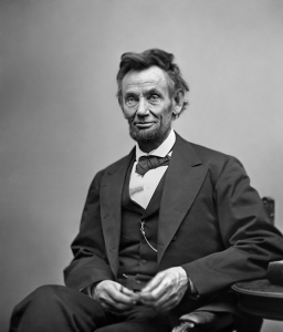 Abraham Lincoln three-quarter length portrait seated and holding his spectacles and a pencil